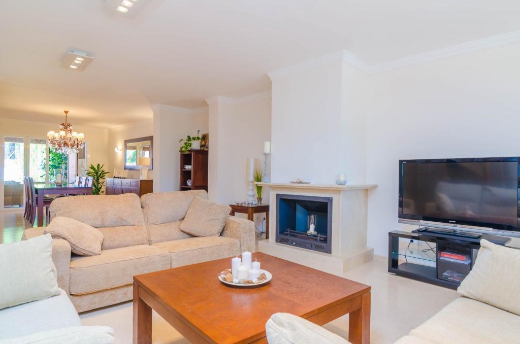 """Der freundliche Wohn- und Essbereich des Ferienhauses """"Villa Gloria"""" auf Mallorca bietet einen Kamin für kühlere Abende"""